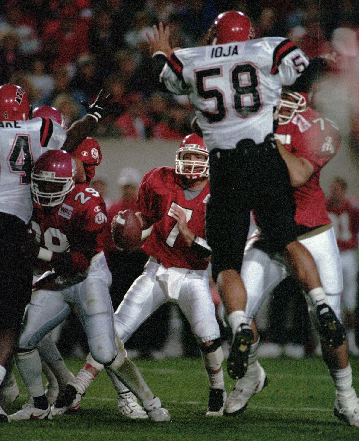 Mike Fouts looks for opening as San diego State players Adrian Ioja (58) and Roger Black defend. ALLRED/photo (Submission date: 10/22/2002)
