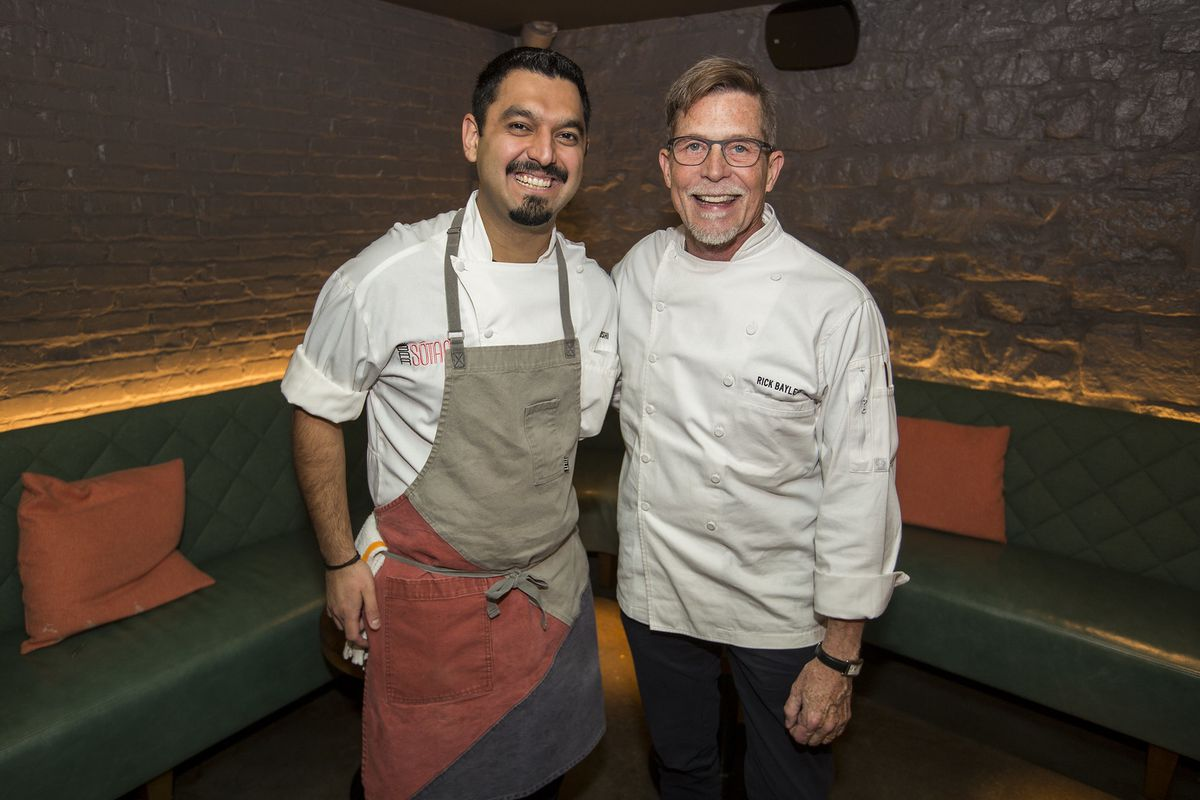 Two chefs standing and smiling next to each indoors.
