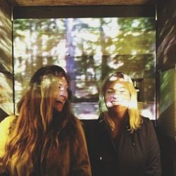 My friend Odile and I spending time in the custom wooden outdoor shower they had created. This is a movie being projected on our faces. It smelled like the woods in there!