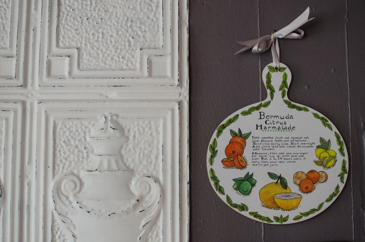 An ancient Greek- or Roman-style white wall panel adorns a dark gray wall, next to a white paddle with a recipe for citrus marmalade painted onto it.