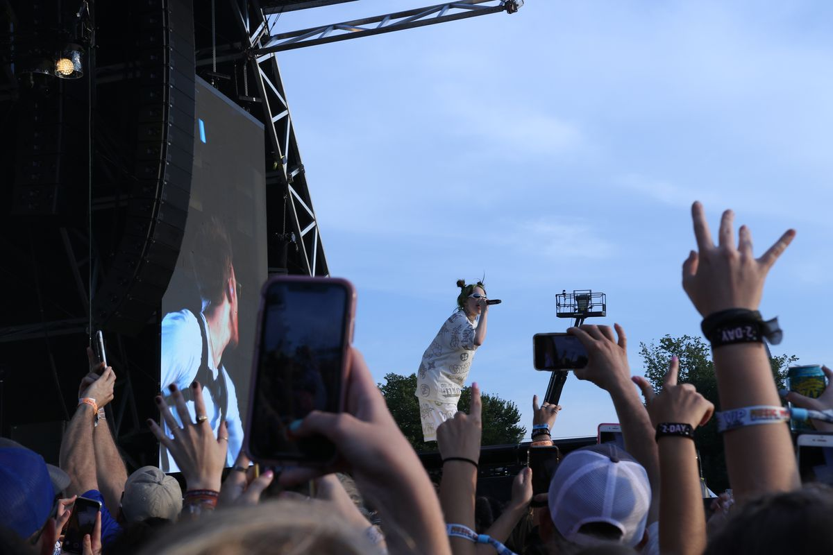 Billie Eilish sings over a rowdy crowd of fans, many of whom are recording on their phones.