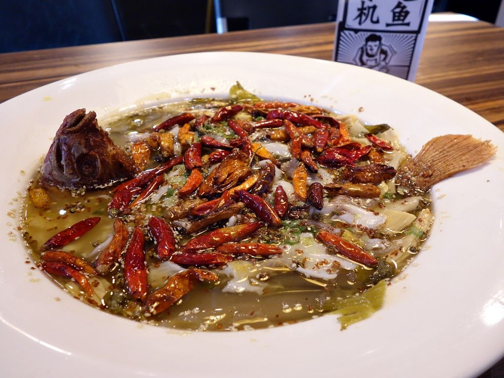 A soup bowl filled with chunks of fish, chiles, Sichuan peppercorns, and a large fish head pointed toward the sky