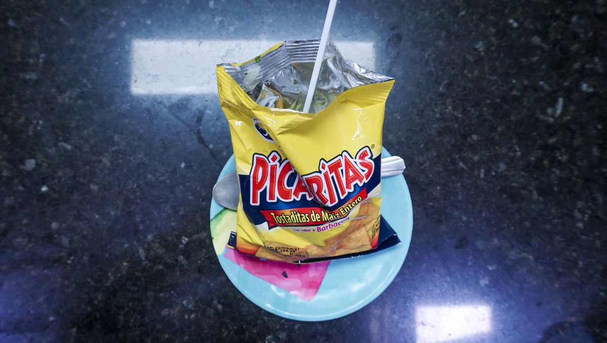 A bag of chips with a fork in it on a plate.