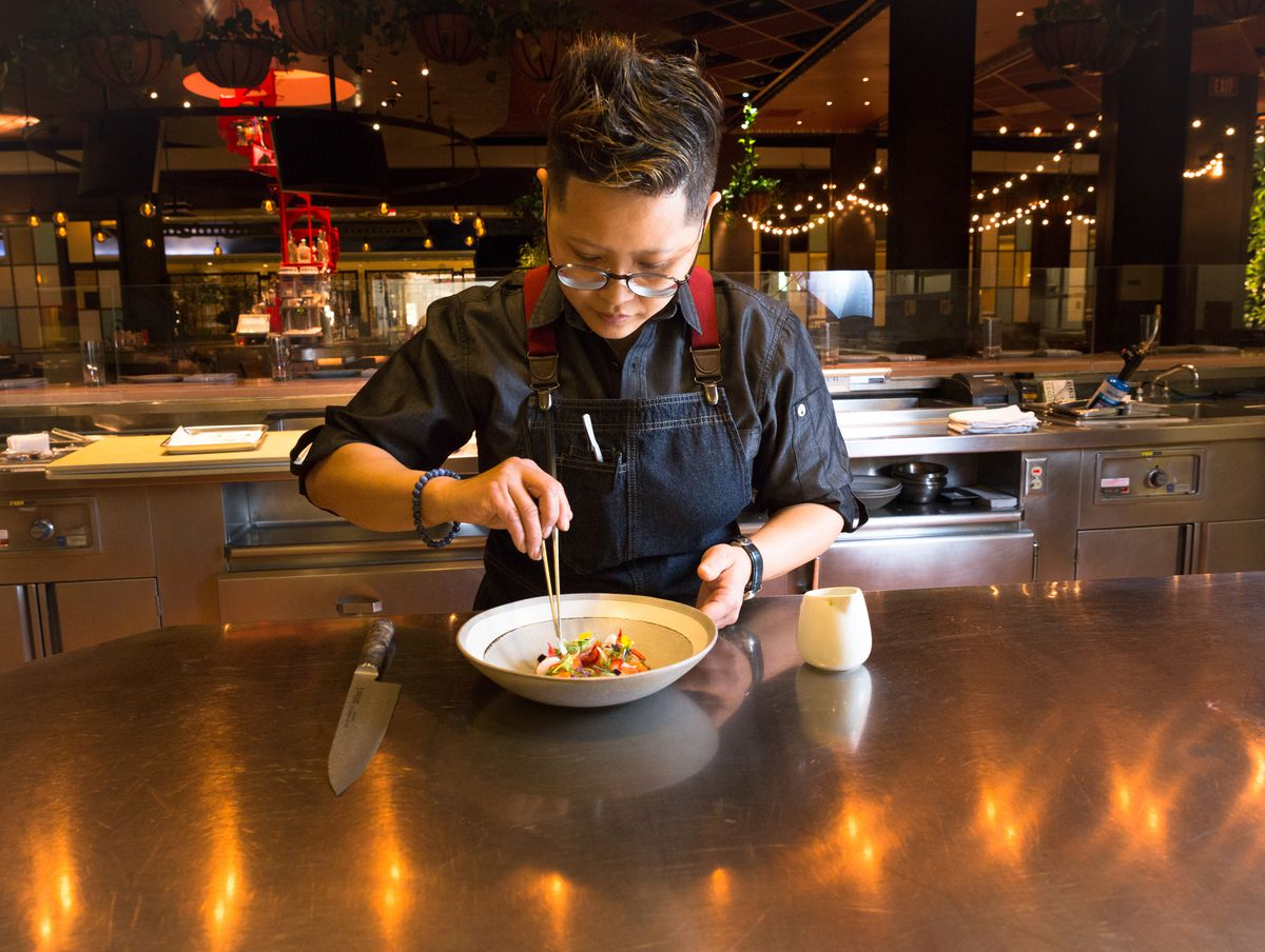 A chef uses a pair of tweezers to put the finishing touches on a dish in a restaurant kitchen