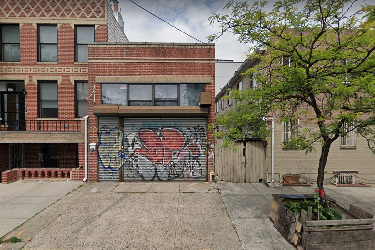 An empty sidewalk leads up to a building with a steel grate covered in graffiti