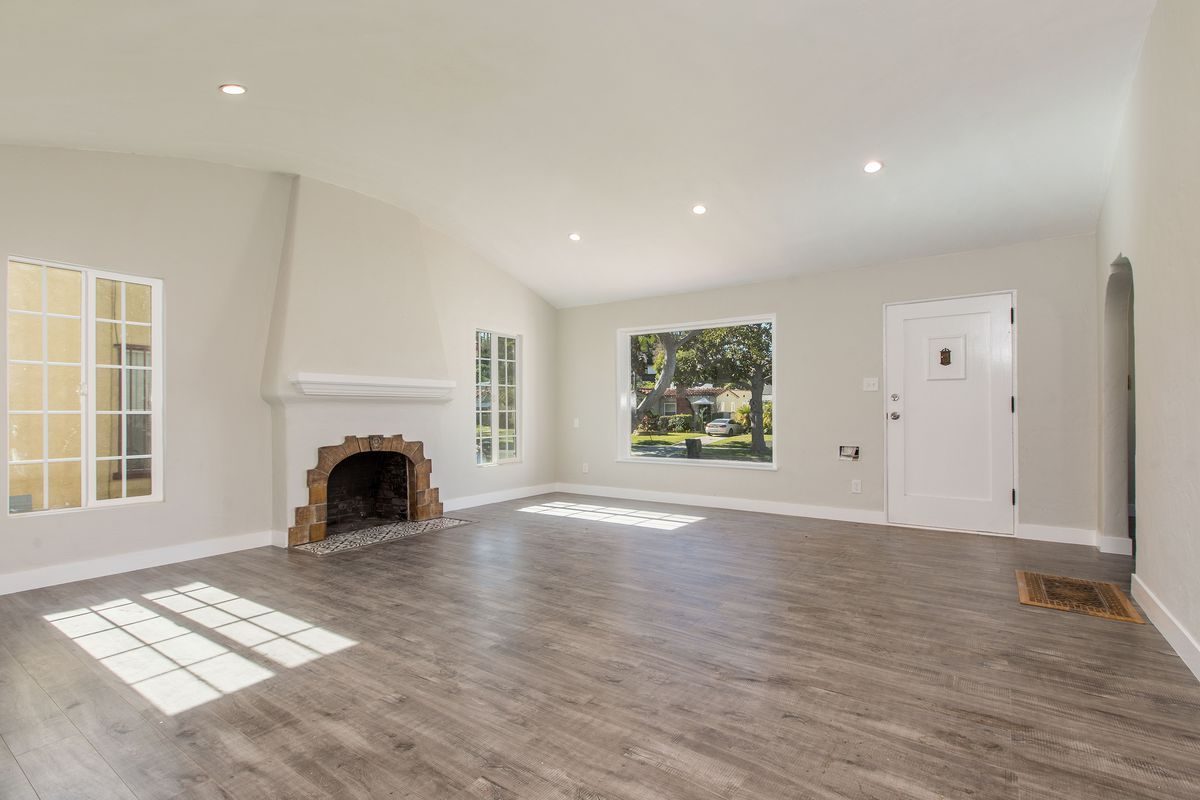 An open space with a tall fireplace and many windows.