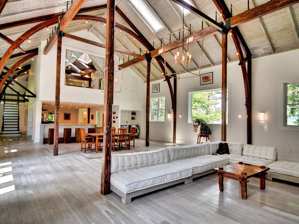 A big, spacious room with a white sectional couch and an arched ceiling that beams are helping hold up.