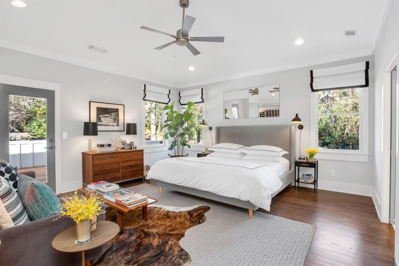 A master bedroom with a couch and deck off the back.