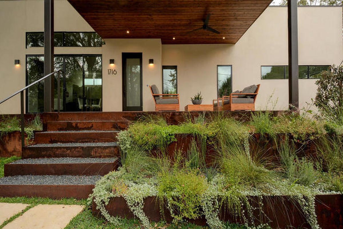 Off-white contemporary porch with rusted metal terraced landscaping and steps leading to large porch with flat wooden roof