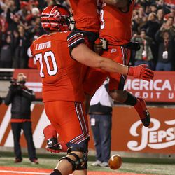 Utah Utes offensive lineman Jackson Barton (70), wide receiver Darren Carrington II (9) and quarterback Troy Williams (3) celebrate after Williams ran for a touchdown, putting the Utes up 21-0 over the Colorado Buffaloes after the PAT, at Rice-Eccles Stadium in Salt Lake City on Saturday, Nov. 25, 2017.