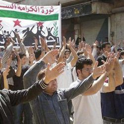 """In this citizen journalism image provided by the Local Coordination Committees in Syria and taken on Friday, April 6, 2012, Syrians chant slogans during a demonstration in Idlib, north Syria. A U.N.-brokered peace deal for Syria appeared to collapse Sunday April 8, 2012 as the government made a new demand that its opponents provide """"written guarantees"""" to lay down their weapons before regime forces withdraw from cities, a call swiftly rejected by the country's main rebel group. The banner with the Syrian revolutionary flag on it and Arabic writing reads, """"dignity revolution in Syria."""""""
