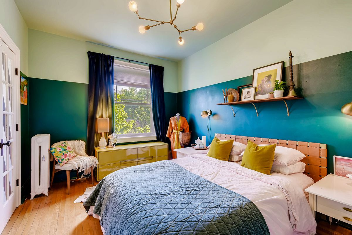 The bedroom features a colorful bedspread, a window, and a hardwood floor. There is an open shelf above the bed.