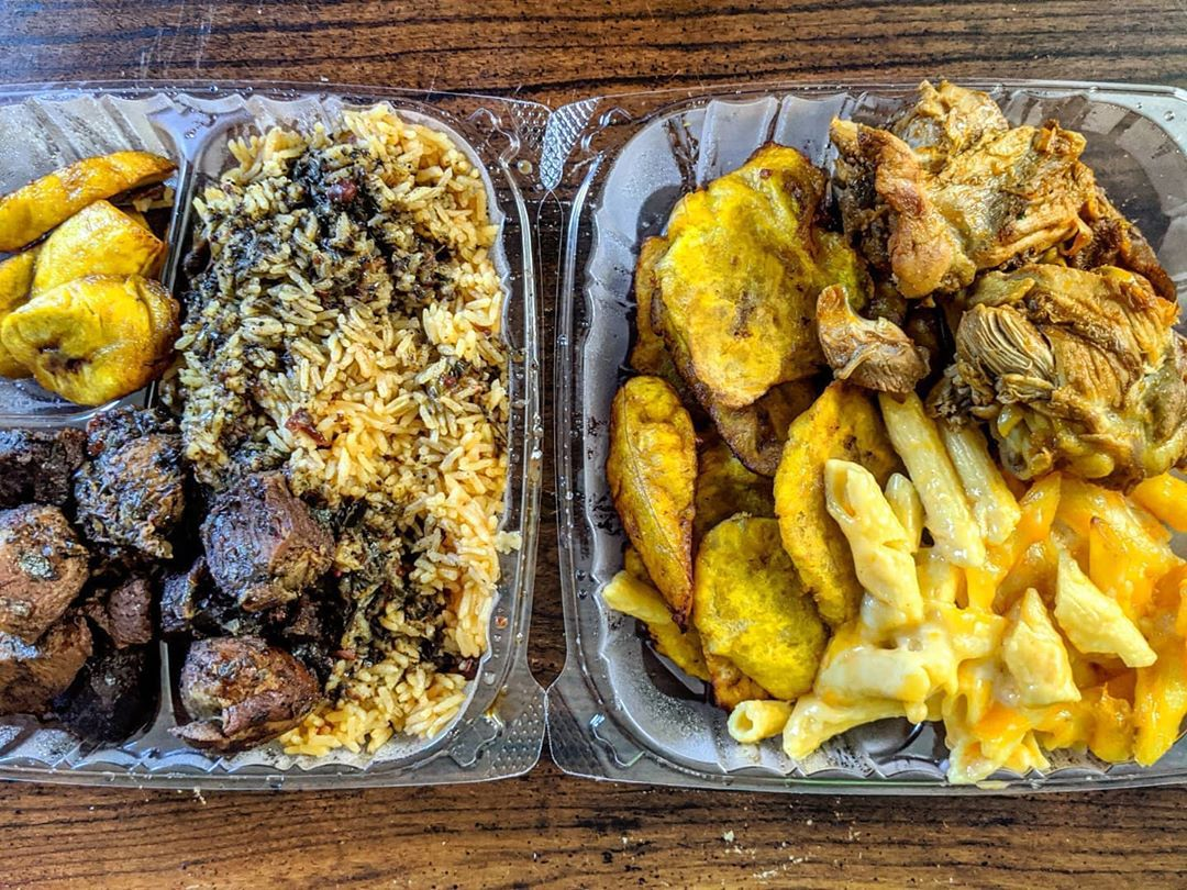 Overhead view of takeout containers with Caribbean food, including pork, chicken, plantains, rice and beans, and more