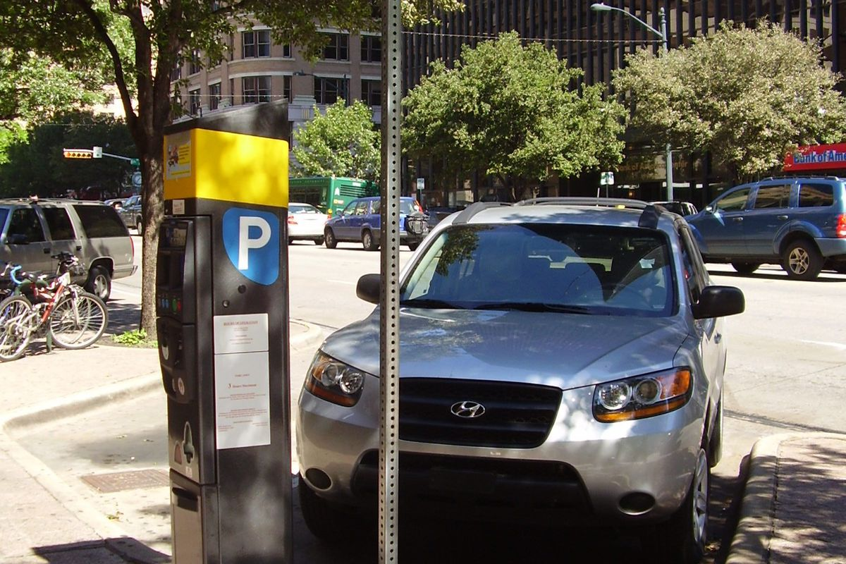 An electronic parking meter kiosk with a yellow top and a big white P on a blue back ground with a car and street behind