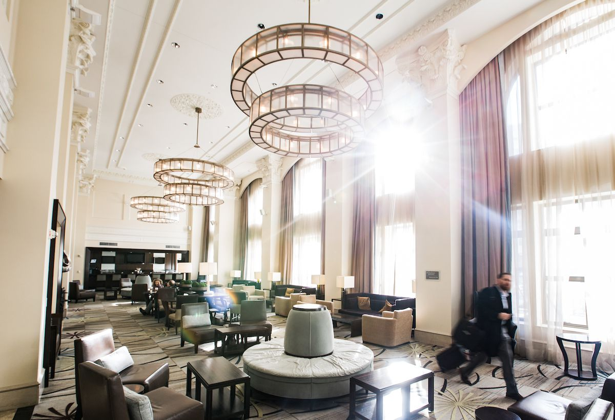 The interior of the Westin Book Cadillac Detroit. The room is painted white with high ceilings and chandeliers. There are multiple tables and chairs. There are floor to ceiling windows letting in natural light.