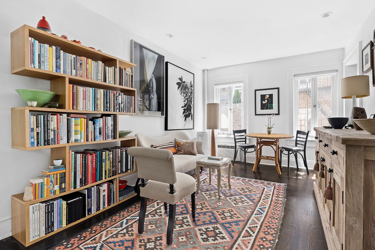 A living area with a bookshelf, two framed windows, hardwood floors, several chairs, and a rug.