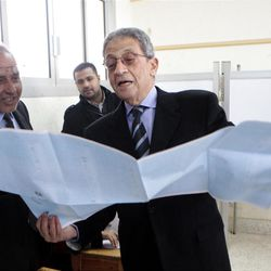 FILE - In this Jan. 30, 2012 file photograph, Amr Moussa, Egyptian presidential hopeful and former secretary general of the Arab League, reads a list of candidates for the upper house of parliament at a polling station in Cairo, Egypt. The presidential election scheduled in May will mark the beginning of a handover of power by the ruling military to an elected civilian, following last year's popular uprising that overthrew Hosni Mubarak.(AP Photo/Amr Nabil, File)