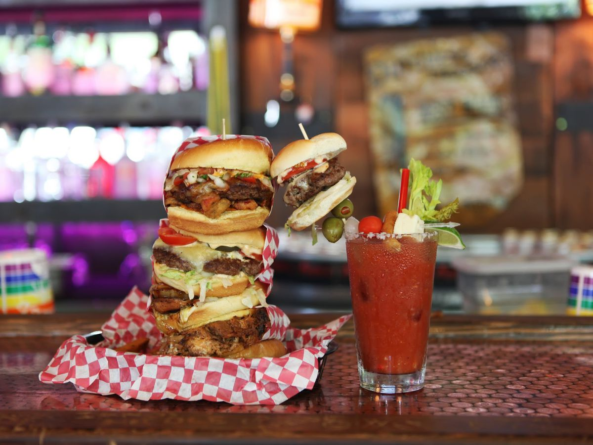 A stack of hamburgers on a bar at Sam's Tavern, next to a bloody mary topped with a beef slider.