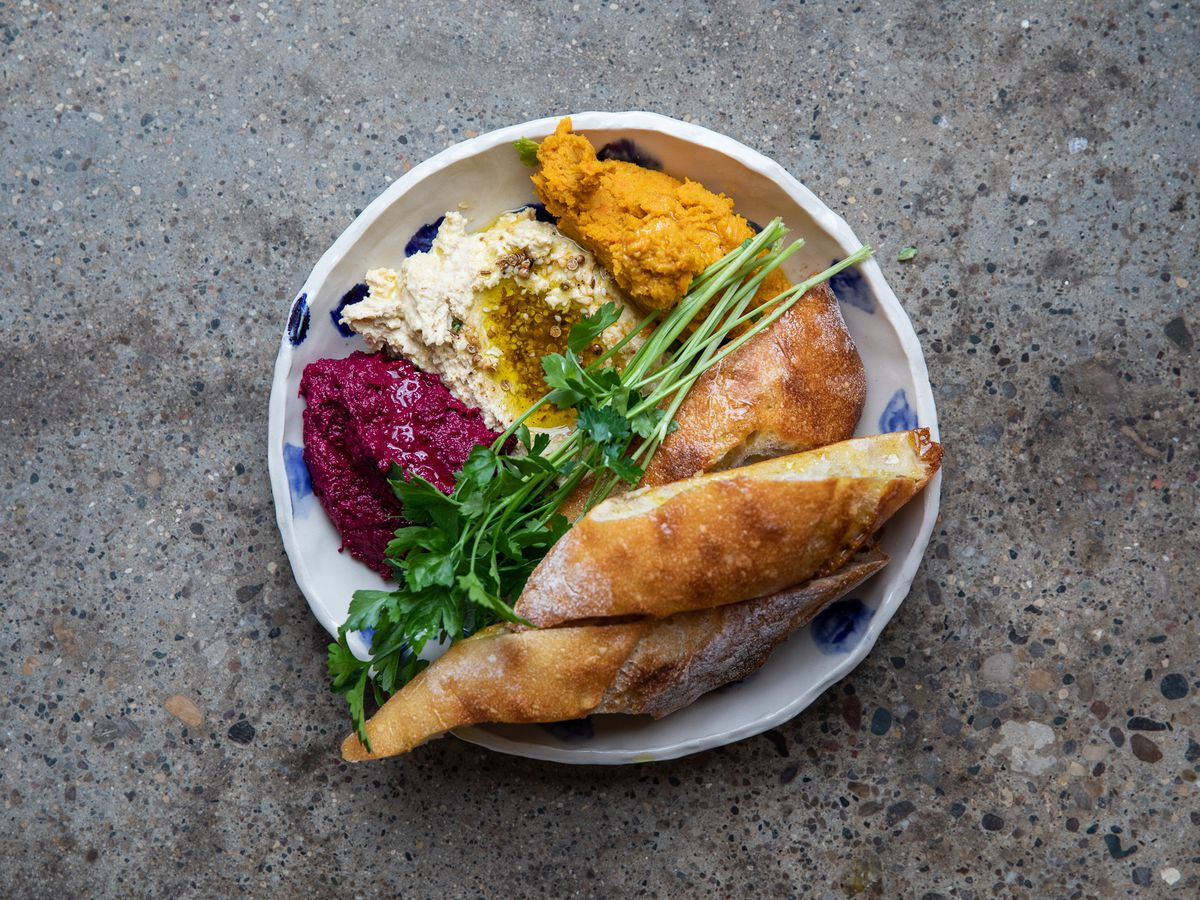 Bread slices and three spreads in beet pink, orange, and beige colors with sprigs of parsley on top sit on a round dish on a concrete background.