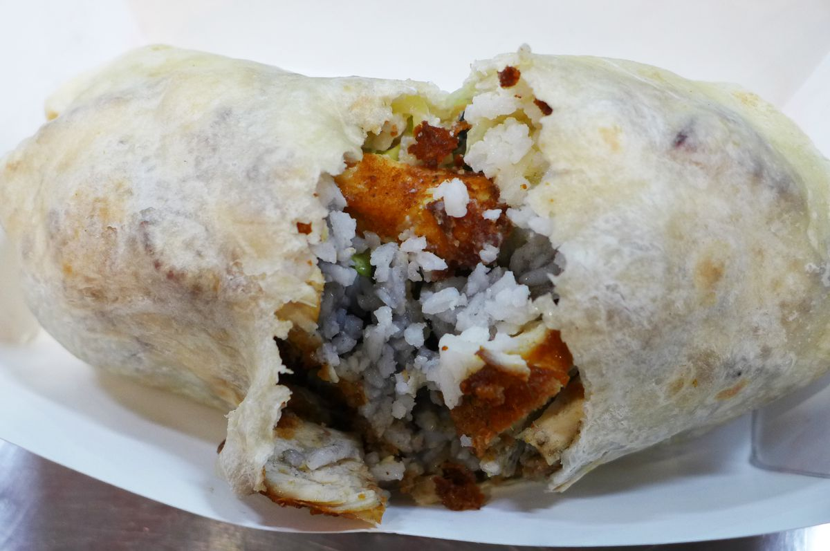 A large diameter burrito is split open to show the rice, beans, and boneless fried chicken inside.