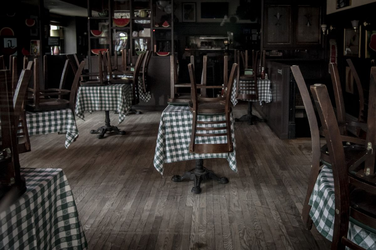 Inside an empty restaurant with upturned chairs placed on tables
