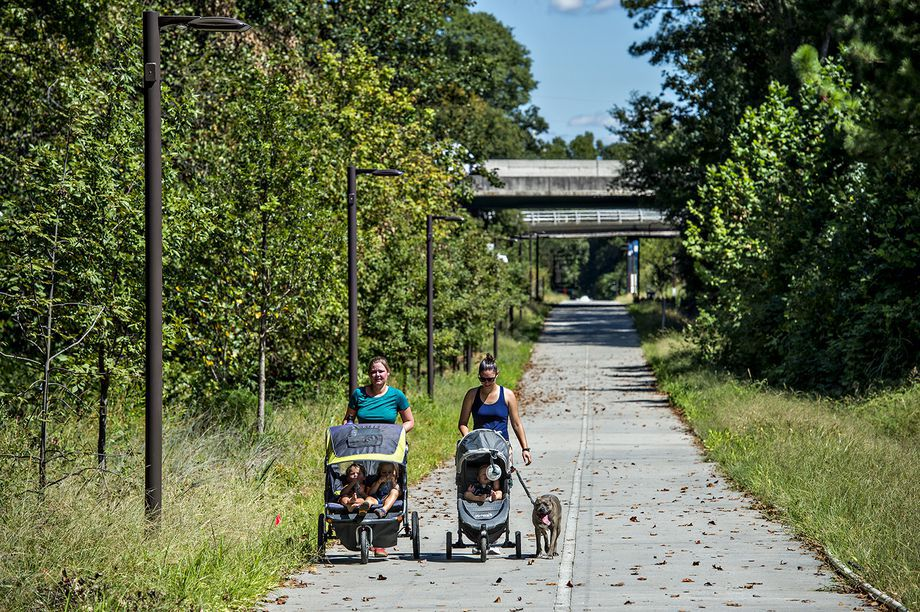 Two women push strollers along a paved path with trees beside it.