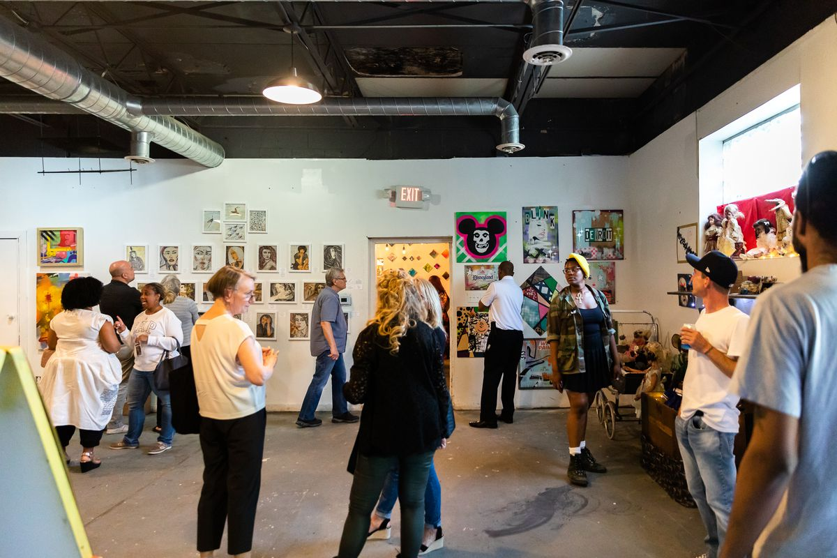 A large room with cement floors and art on the white walls. People mingle and look at the art.