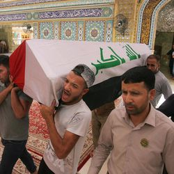 Mourners carry the Iraqi flag-draped coffins of bomb victims, Talib Hassan, 35, and Hamza Jabbar, 37, during their funeral procession at the holy shrine of Imam Ali in Najaf, 100 miles (160 kilometers) south of Baghdad, Iraq, Sunday, July 3, 2016. Dozens of people have been killed and more than 100 wounded in two separate bomb attacks in the Iraqi capital Sunday morning, Iraqi officials said.