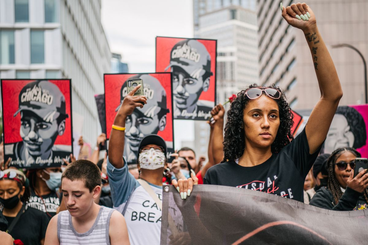 """A Black woman with long curly hair holds up a fist; behind her is a dense crowd, many of the marchers holding up black and white portraits of Daute Wright, wearing a baseball cap that says """"Chicago."""""""