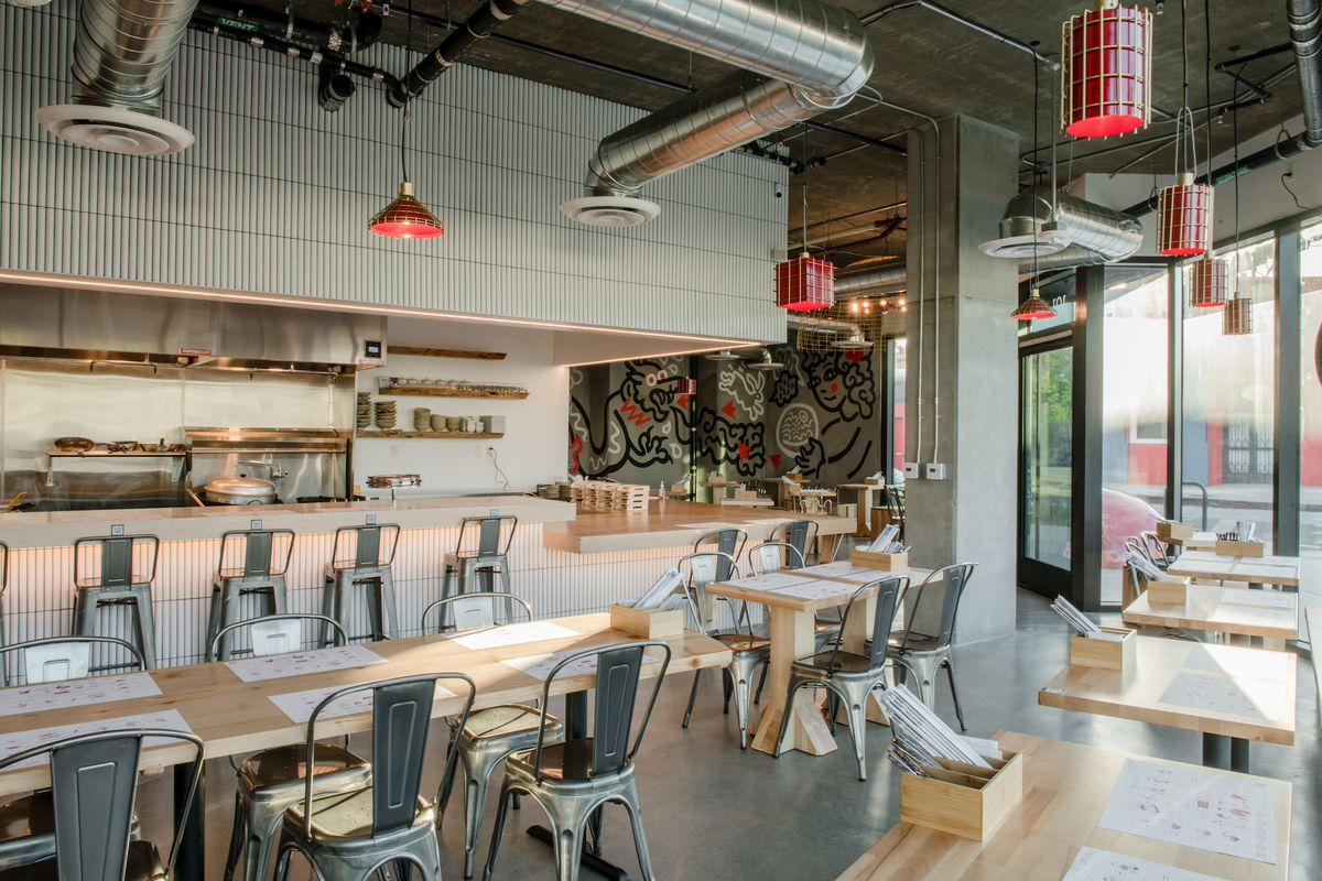 A new industrial restaurant with open venting in the ceiling and wooden tables.