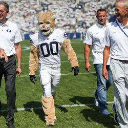Marc Wilson, Luke Staley and Robbie Bosco, who played under the to-be-retired jersey #6, walk with Cosmo the Cougar before the game against the Wisconsin Badgers at LaVell Edwards Stadium in Provo on Saturday, Sept. 16, 2017.