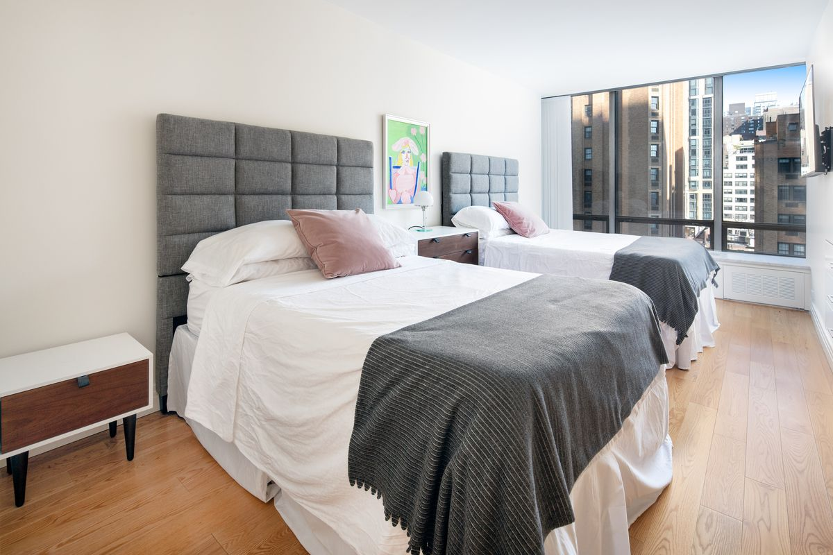 A bedroom with two medium-sized beds, a large window, and hardwood floors.