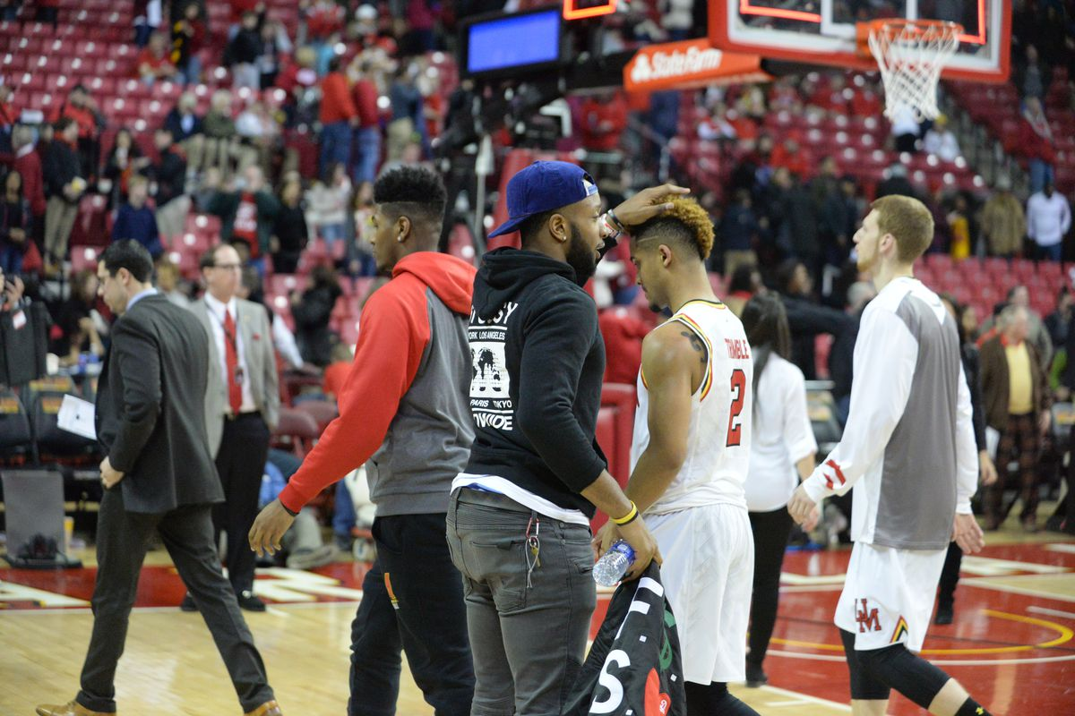 Former Maryland guard Dez Wells consoles Melo Trimble after the Terps' loss to Wisconsin on Saturday.