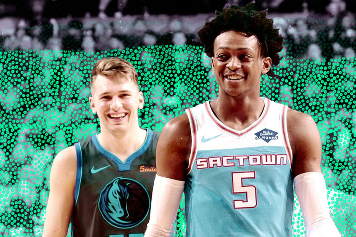 De'Aaron Fox (foreground) and Luka Doncic (background) smile during a game.
