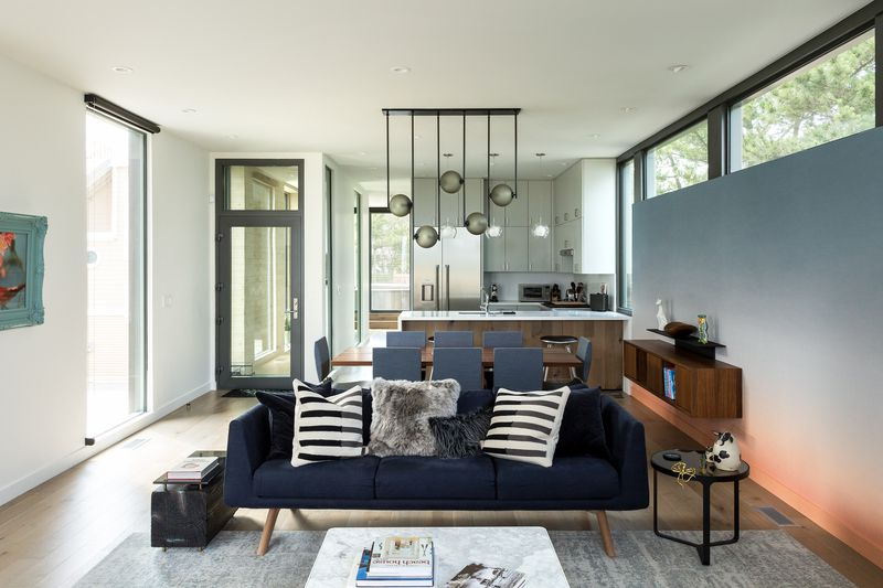 An open living room, dining room, and kitchen with a navy sofa, rectangular dining table surrounded by gray chairs, white countertops, and sculptural pendant lighting featuring pearlescent spheres.