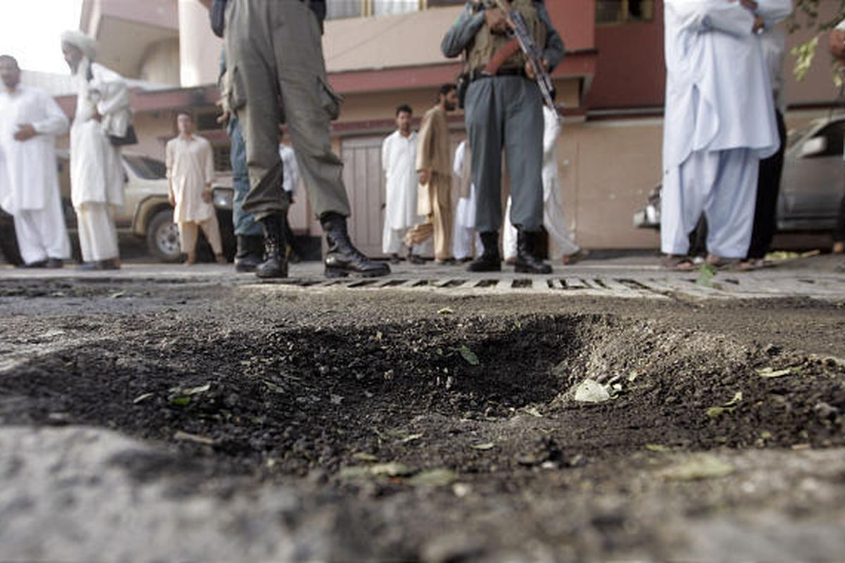 Afghan police men stand  next to a crater following a rocket attack near U.S embassy in Kabul, Afghanistan, Tuesday.