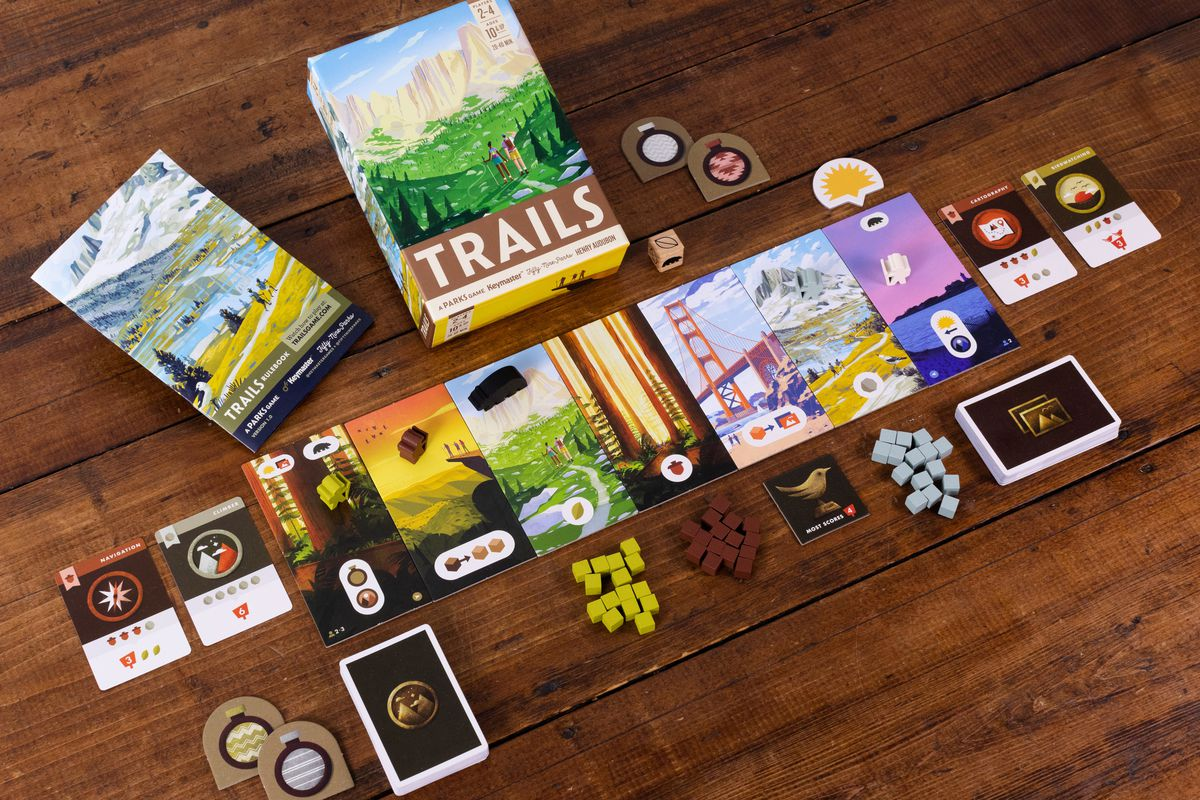A game of Trails set up to play, including piles of resources — acorns, stones, and leaves — along the bottom of the board.