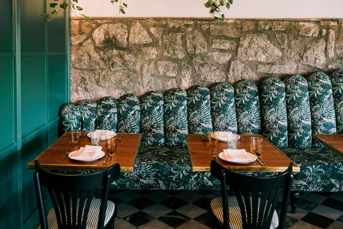 A banquette with scalloped cushions and a deep green and white fern print.
