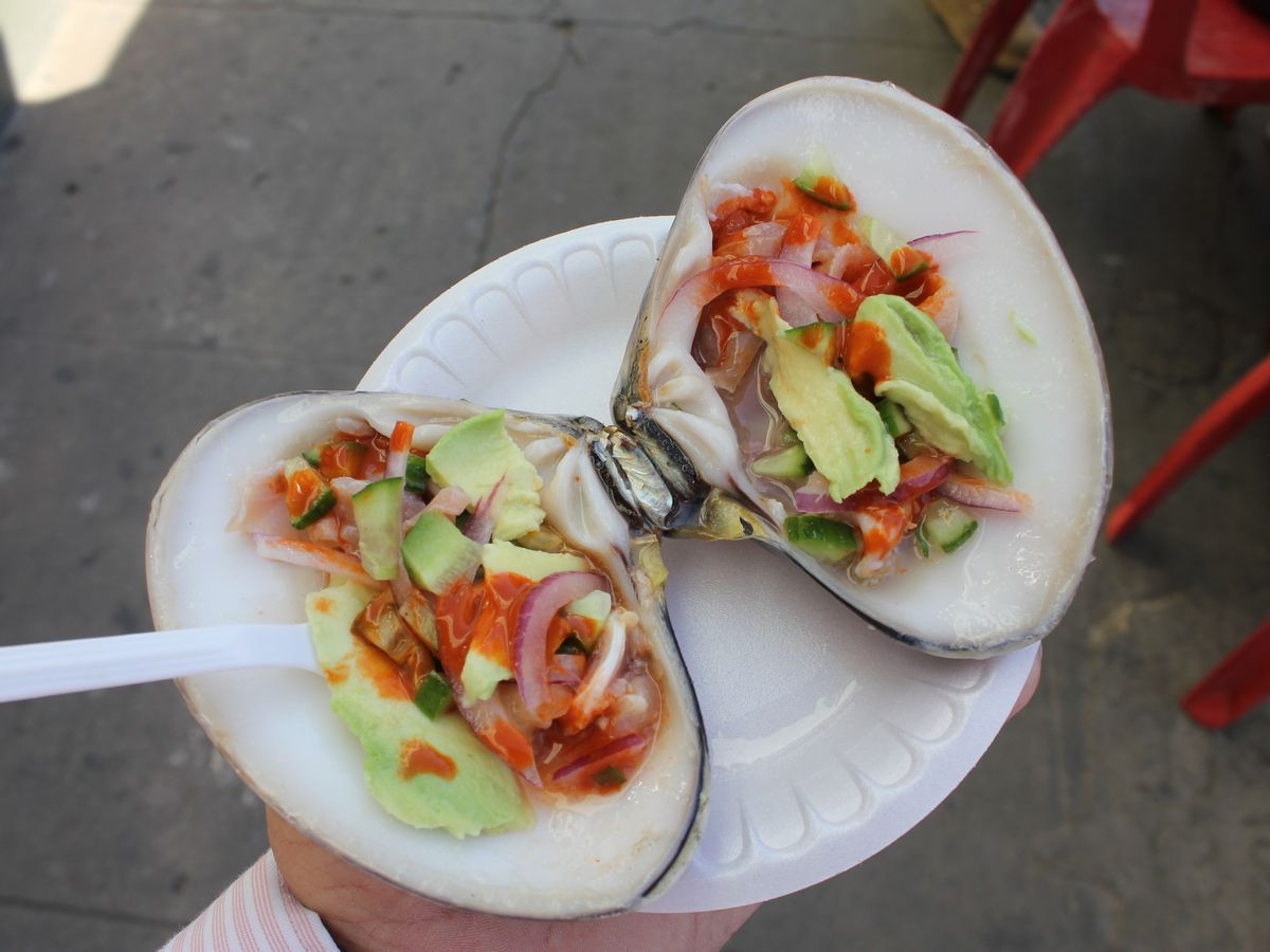 A huge clam, split open, fills a paper plate a hand holds above a concrete floor. The clam is topped with slices of avocado, red onion, and red sauce, with a plastic fork sticking out