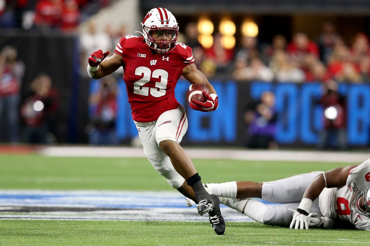 Jonathan Taylor #23 of the Wisconsin Badgers runs the ball in the Big Ten Championship game against the Ohio State Buckeyes at Lucas Oil Stadium on December 07, 2019 in Indianapolis, Indiana.