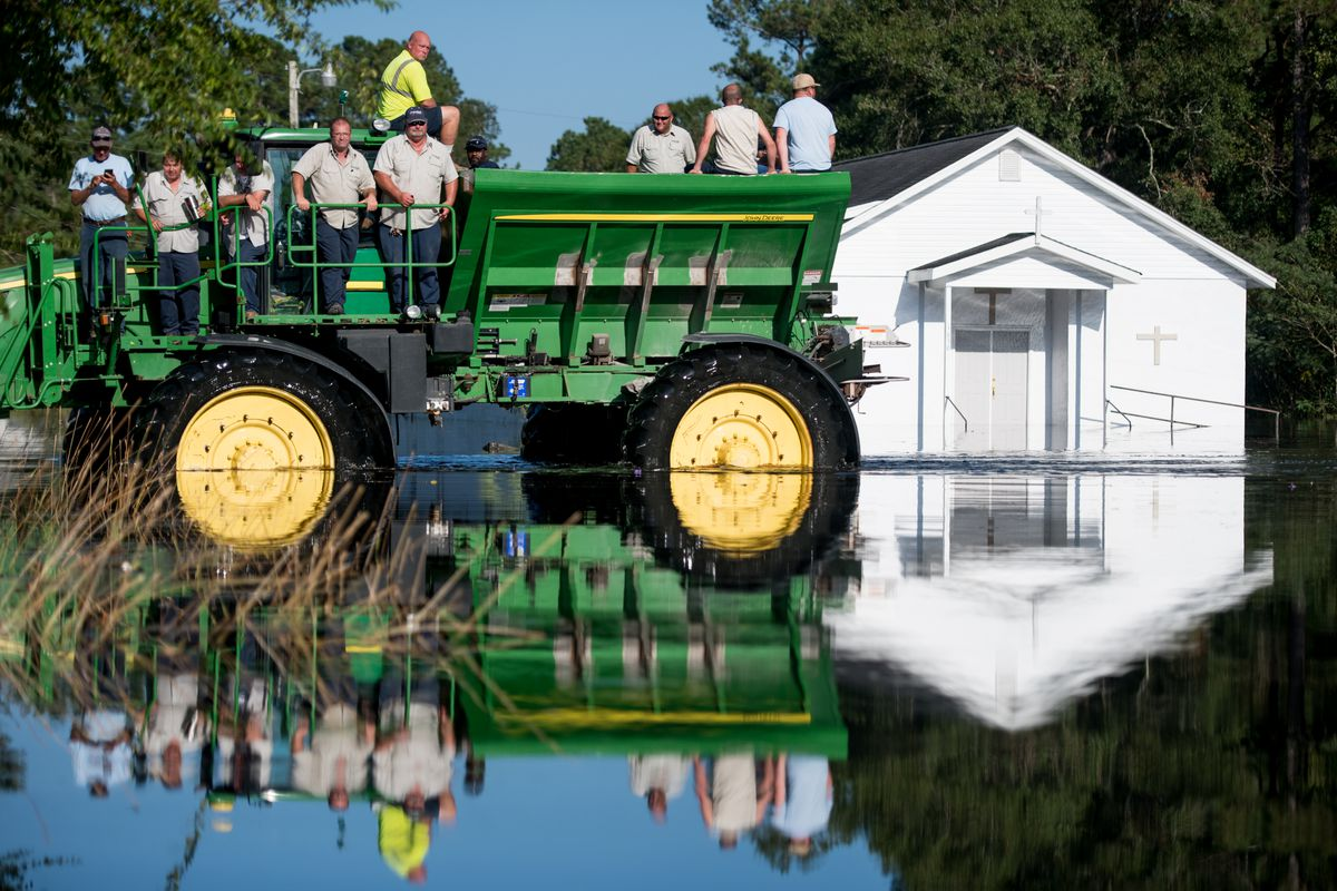 Workers uses farm machinery to navigate floodwaters from the Waccamaw River caused by Hurricane Florence in Bucksport, South Carolina.