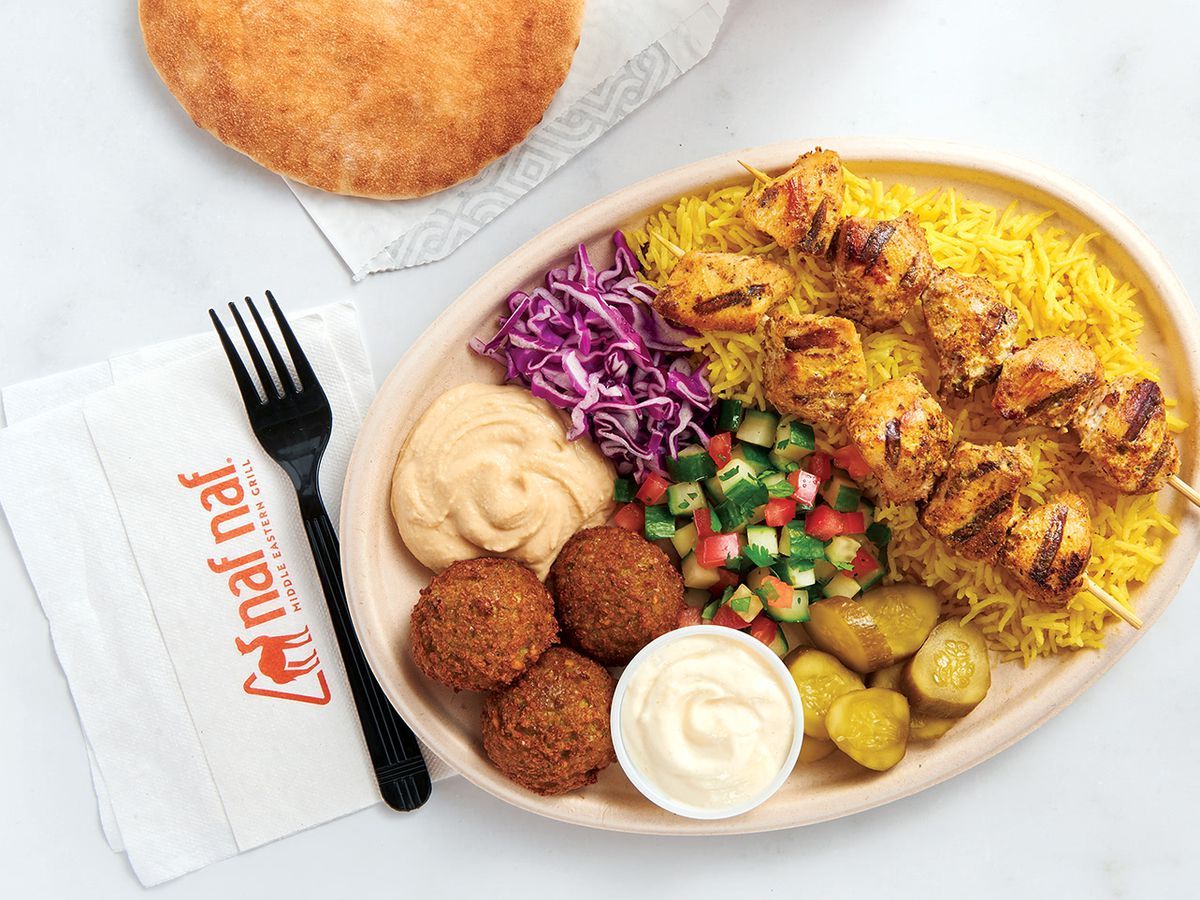 A chicken kebab plate filled with rice, falafel, hummus, and veggies