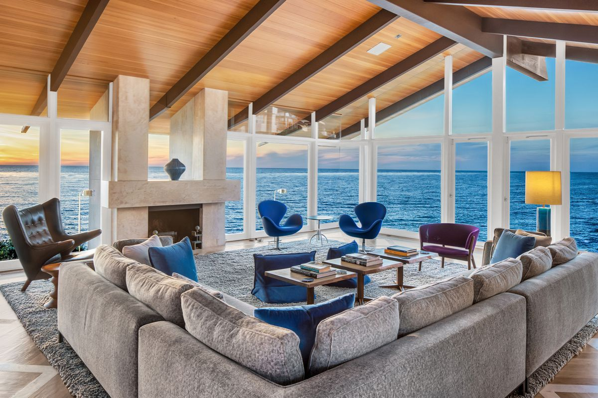 A living room with a gray couch, coffee table, fireplace, and walls of glass looking out to the blue ocean.