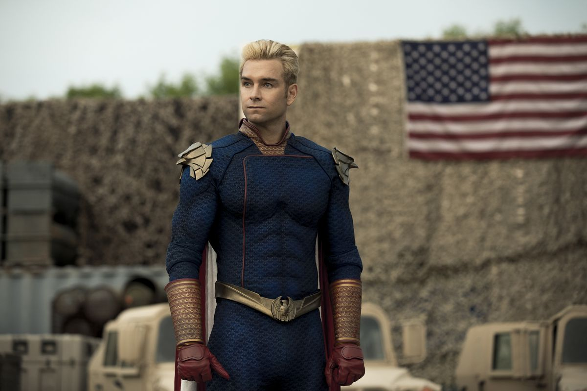 Homelander stands on a military base in front of an American flag in The Boys season 2