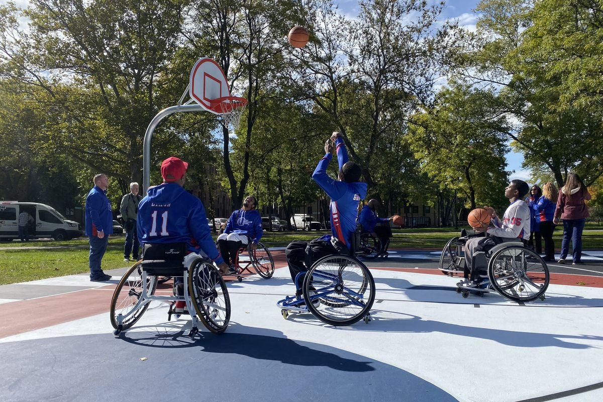 A group of men in wheelchairs play basketball on a court with fresh paint of blue, white, and red.