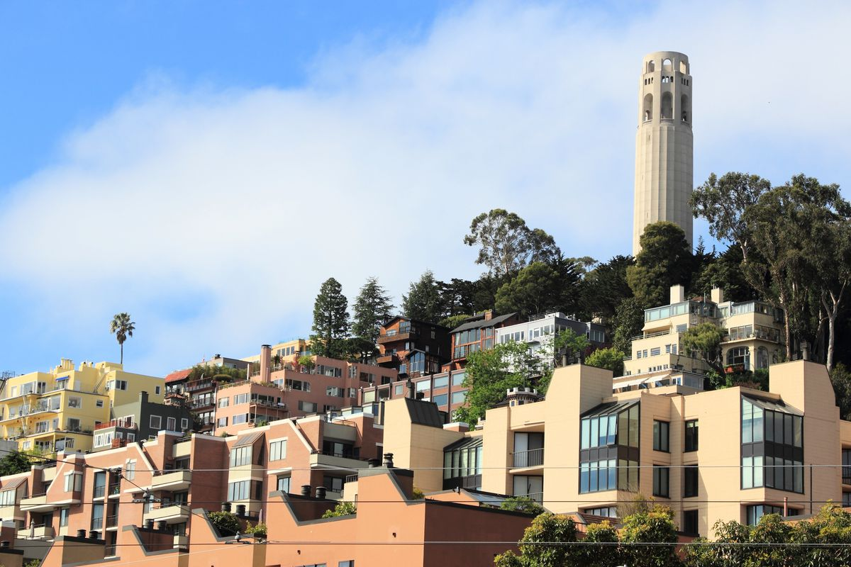 Coit tower rising on a hill behind some San Francisco apartments.