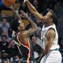 Boston Celtics shooting guard Avery Bradley, right, reaches up to block a shot by Milwaukee Bucks point guard Brandon Jennings, left, during the second quarter of an NBA basketball game in Boston, Thursday, April 26, 2012.