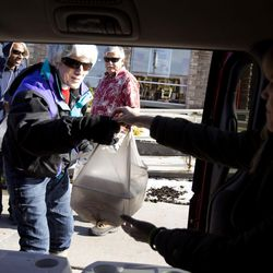 A homeless man is offered a hot Thanksgiving Day meal as Ed Snoddy, Pamela Atkinson and DeAnn Zebelean, of the Volunteers of America-Utah homeless outreach, deliver meals to homeless people in Salt Lake City on Thursday, Nov. 24, 2016.