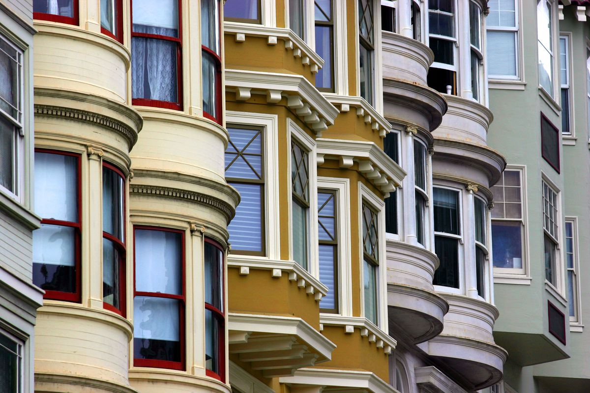 A series of Victorian bay windows angled uphill, in an array of colors like yellow, green, and pink.
