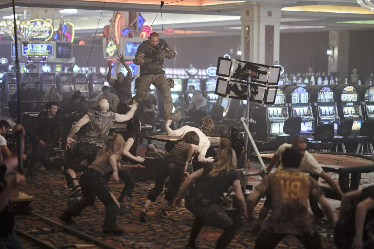 Dave Bautista, on a wire rig, runs across tables in a casino as actors playing zombies chase him in a behind-the-scenes image from Army of the Dead